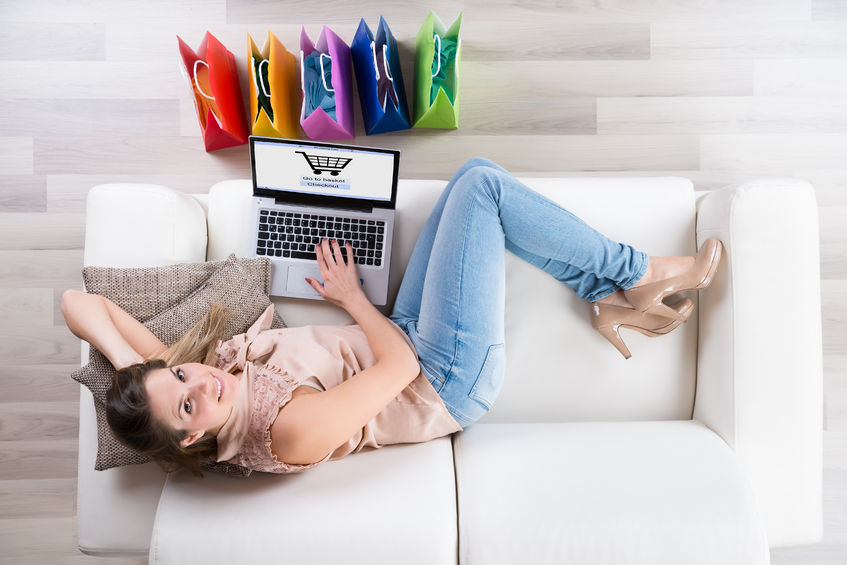 51924942 - young happy woman on sofa shopping online with laptop